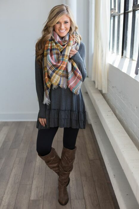 Girl wearing long red checked scarf, gray, and navy blue dress with black stockings and brown high boots