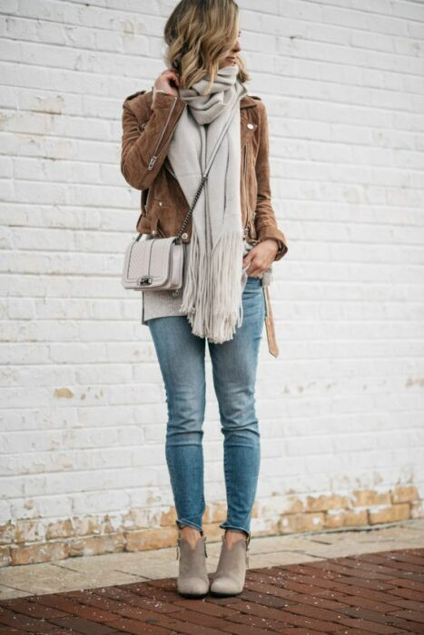 Girl wearing long gray scarf, jeans and camel jacket