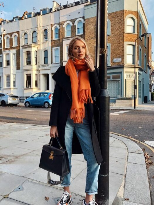 Girl wearing long orange scarf, jeans and black coat