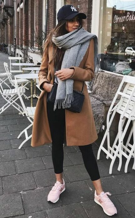 Girl wearing long gray scarf, black blouse and jeans and camel coat