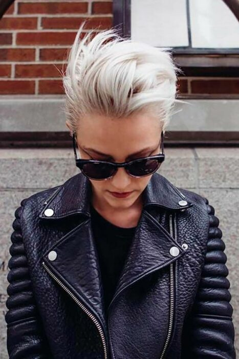 Girl in black blouse and black leather jacket looking down with dark glasses and pixie cut in white tone 'icy blonde'