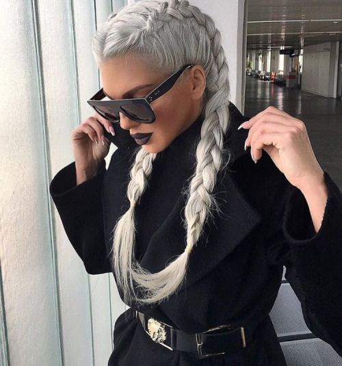 Girl in black blouse and jacket and square sunglasses with 'icy blond' hair styled in two French braids and looking down