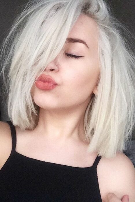White girl doing 'duck face' with black tank top with short hair in 'icy blond' tone