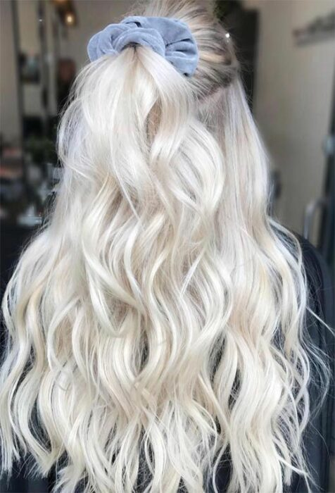 Girl from behind with long curly hair in 'icy blonde' tone held in half ponytail with pastel blue scrunchie