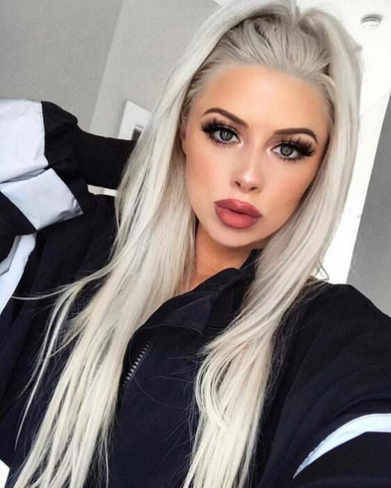 Girl with gray eyes and thick pink lips wearing a black sweatshirt with white stripes on the sleeves with long hair in a half ponytail in an 'icy blonde' tone