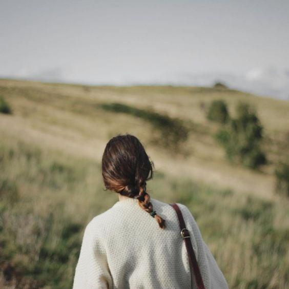 Chica con suéter blanco y trenza mirando hacia un campo verde