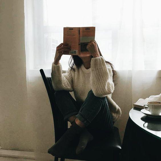 Chica con suéter blanco leyendo un libro