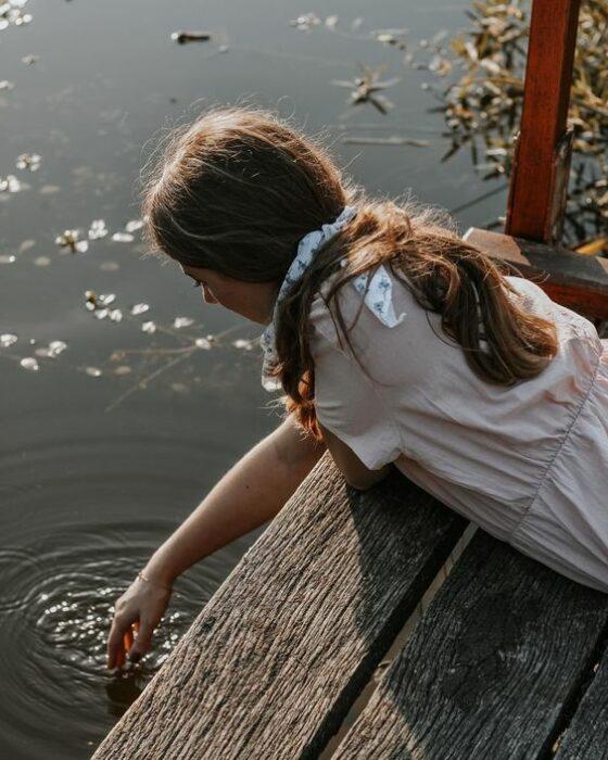 Chica tocando al agua de un lago con la mano