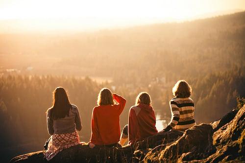 Chicas sentadas en la orillas de una colina mirando el atardecer