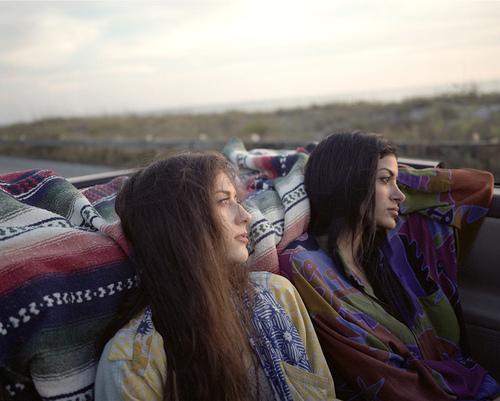 Chica de cabello suelto sentadas en la parte trasera de un coche convertible