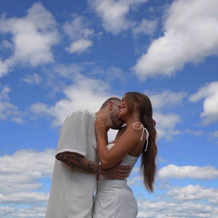 Pareja con ropa blanca besándose con el cielo de fondo