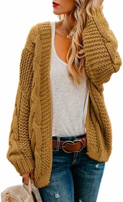 Chica usando cardigan largo color mostaza, con playera beige y jeans