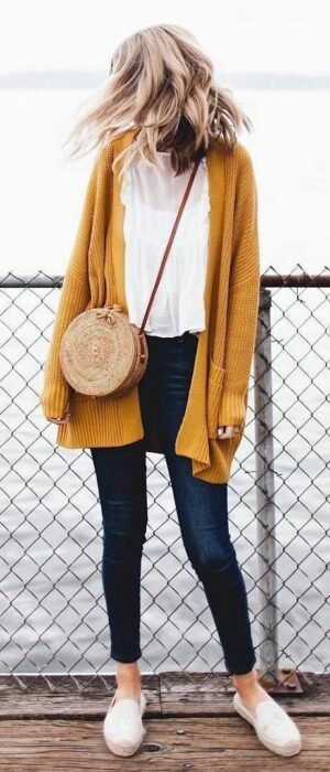 Girl wearing long mustard cardigan, with white blouse, leggings and white tennis shoes