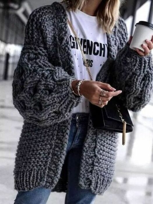 Girl wearing long gray cardigan, and white shirt with print, jeans and black handbag