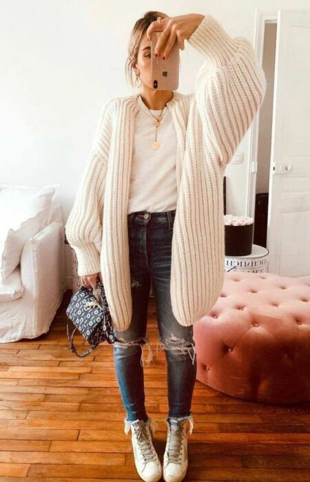Girl wearing long pearl colored cardigan, white blouse and ripped jeans with white ankle boots