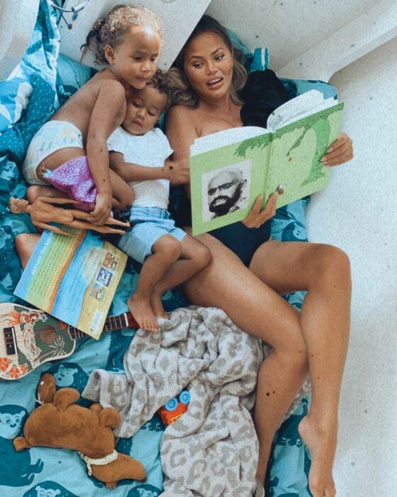 Chrissy Teigen recostada junto a sus hijos leyendo un libro