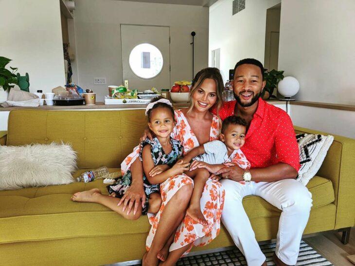 Chrissy Teigen y John Legend posando para una foto mientras están junto a sus hijos