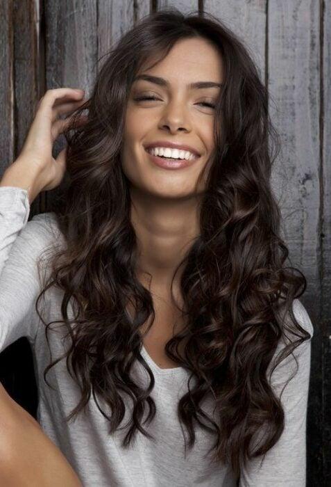 Girl smiling showing her hair in waves in dark brown color
