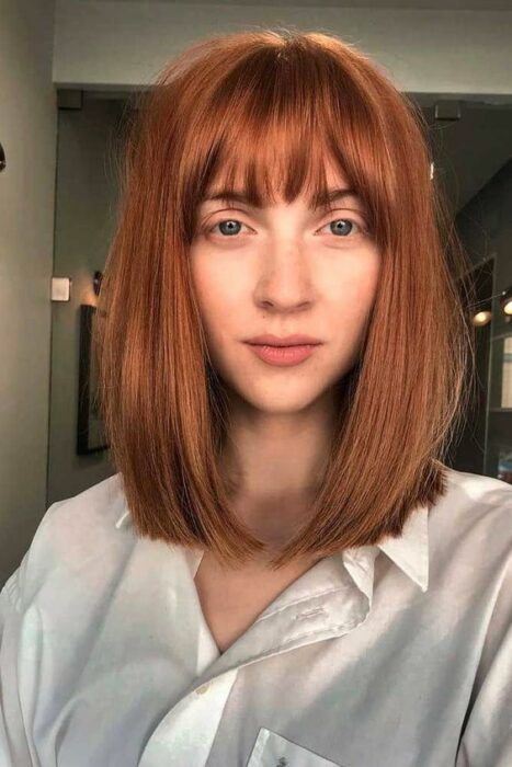 Girl with hair cut in bangs and dyed in copper tone