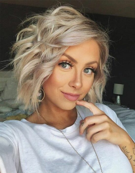 Blonde girl with short hair combed with curls with iron