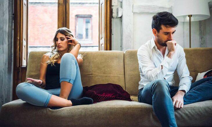 Mujer rubia con cabello ondulado, blusa de tirantes negra y jeans claros recarga su mano izquierda en su cabeza mientras hace gesto de disgusto a lado de un hombre con barba, camisa blanca y jeans oscuros que apoya su mano derecha en su barbilla mientras tiene cara de pensativo; ambos están sentados en un sillón beige