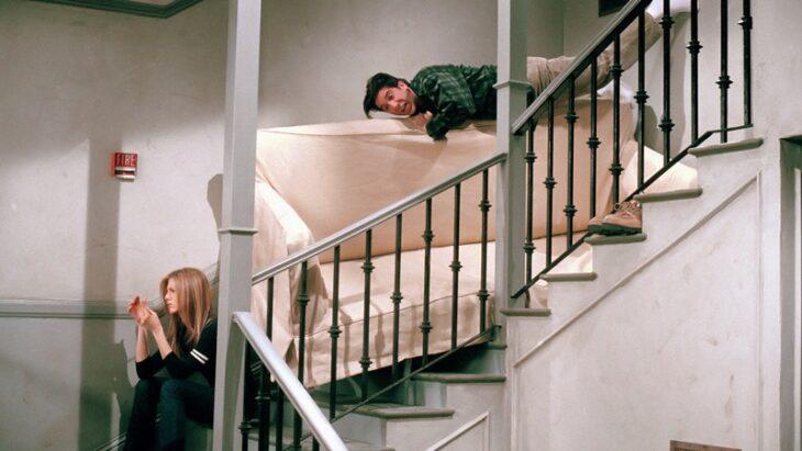 RACHEL Y ROSS de friends en las escaleras de un edificio tratando se bajar un sillón beigr
