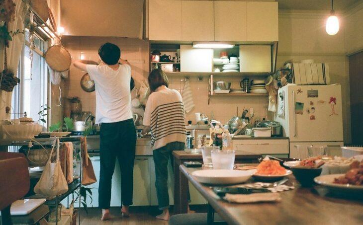 Hombre de playera blanca y pantalón negro y mujer bajita de melena corta con pantalones de mezclilla y suéter blanco con rayas negras cocinando