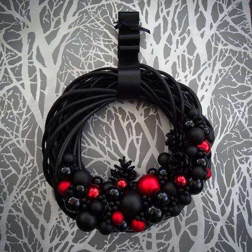 Corona navideña decorada en tonos negros con color rojo