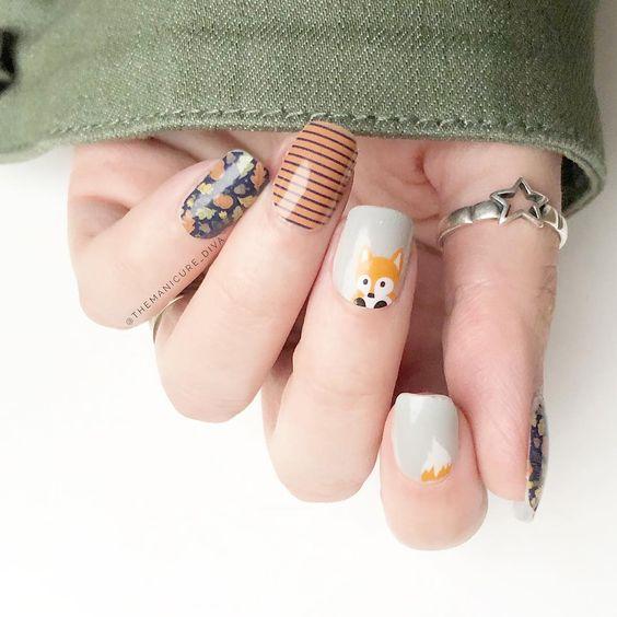 Manicura en color otoñales con dibujo de un pequeño zorro