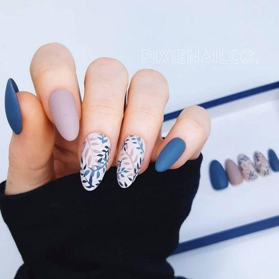 Manicura en tonos azules y diseño a flores
