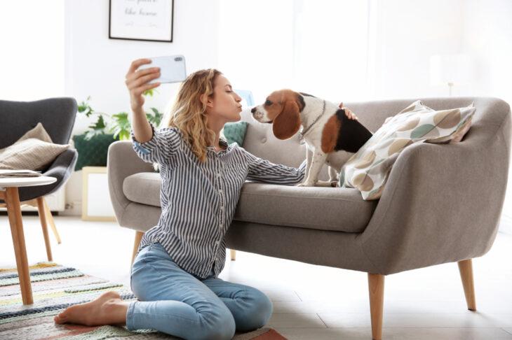 Los mejores celulares smartphone para tomar selfies bonitas; mujer rubia de blusa formal de rayas blancas y negras, pantalón de mezclilla azul claro, sentada en el suelo de la sala tomándose una fotografía con su perro beagle color blanco con manchas cafés y negras