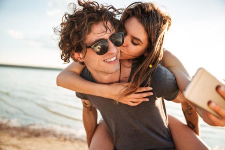 Los mejores celulares smartphone para tomar selfies bonitas; pareja en la playa, hombre cargando a mujer en la espalda, beso en la mejilla, novios tomándose una fotografía