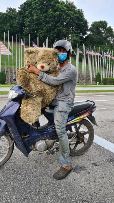 Hombre en motocicleta cargando un oso de peluche