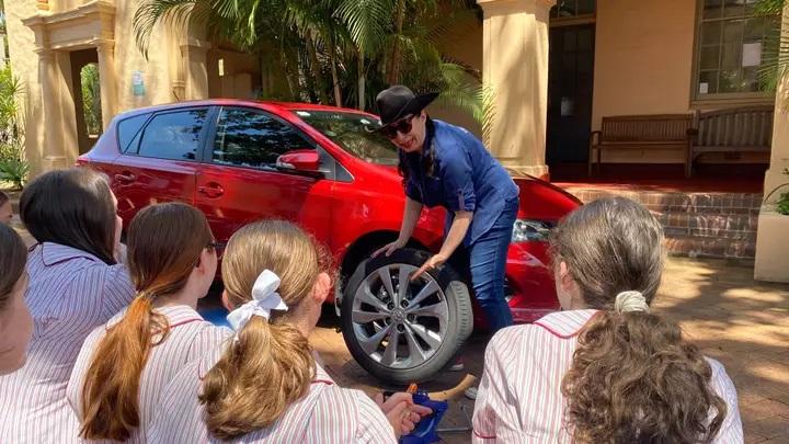 Mujer explicando a niñas como cambiar un neumático