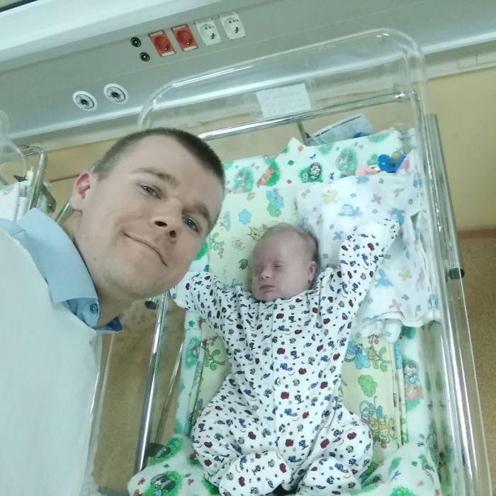 Papá tomándose una selfie junto a su hijo mientras el bebé está en los cuneros
