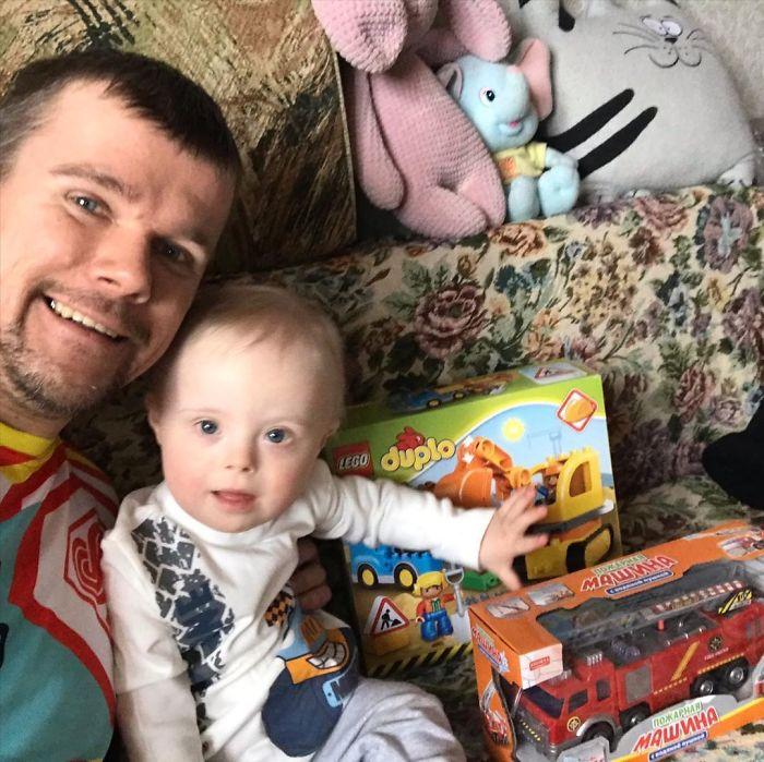 Papá jugando junto a su pequeño con síndrome de Down mientras están sentados en un sofá