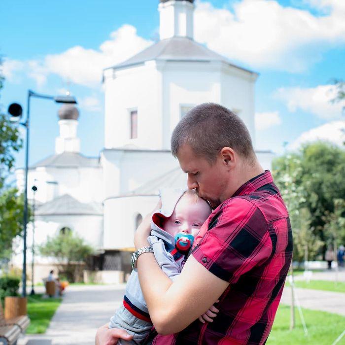 Hombre paseando junto a su hijo y besándolo en la frente