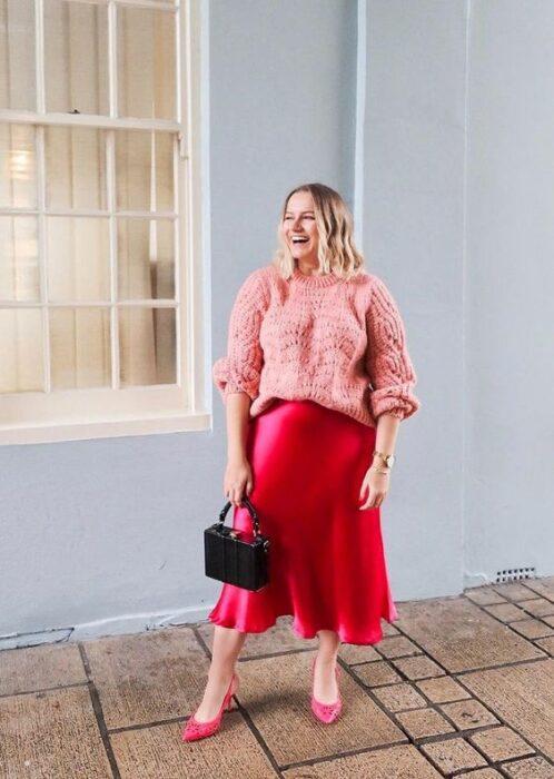 Chica plus size vrubia de cabello suelto ondulado vistiendo una falda de satín roja, suéter rosa y bolso de mano negro