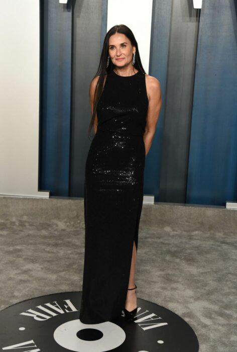 Demi Moore posando con un vestido negro durante una alfombra roja