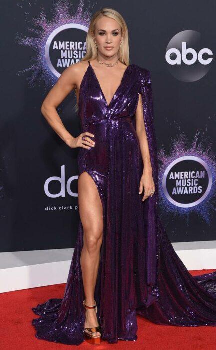 Carrie Underwood posando con un vestido de color morado durante una alfombra roja