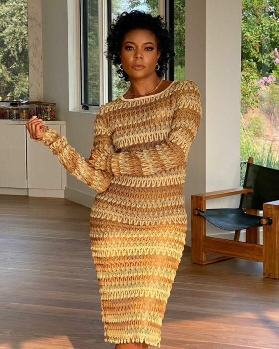 Gabrielle Union posando para una fotografía mientras usa un vestido de color mostaza