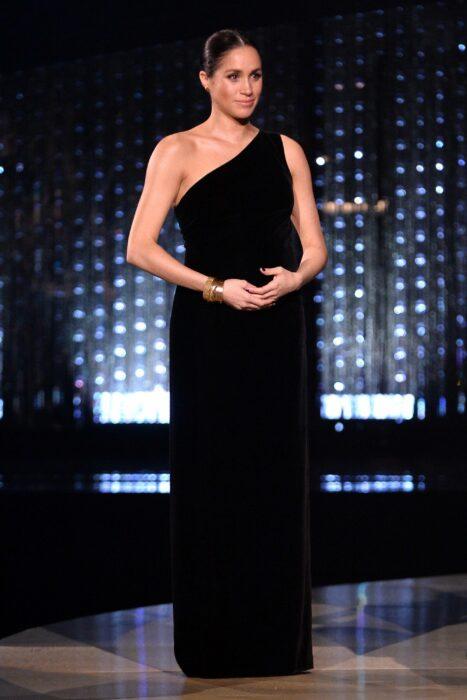 Meghan Markle usando un vestido de color negro mientras está presentando un premio