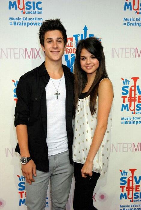 Selena Gomez y David Henrie abrazados mientras posan para una fotografía en la alfombra roja