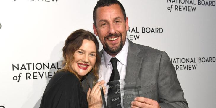 Adam Sandler y Drew Barrymore abrazados mientras posan juntos después de recibir un premio