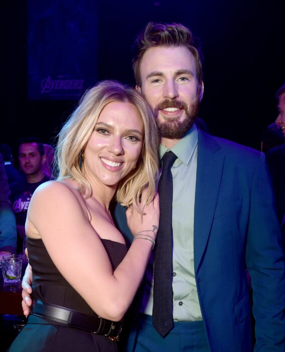 Scarlett Johansson y Chris Evans abrazados mientras posan juntos para una fotografía en una cena