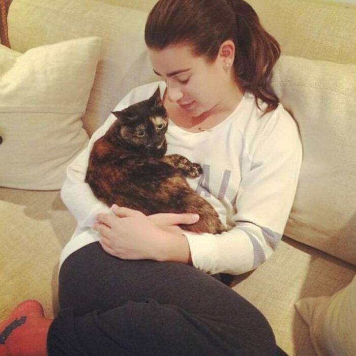 Famosos que han adoptado mascotas, perros o gatos; Lea Michele sentada en el sillón abrazando a su gata carey, Sheila