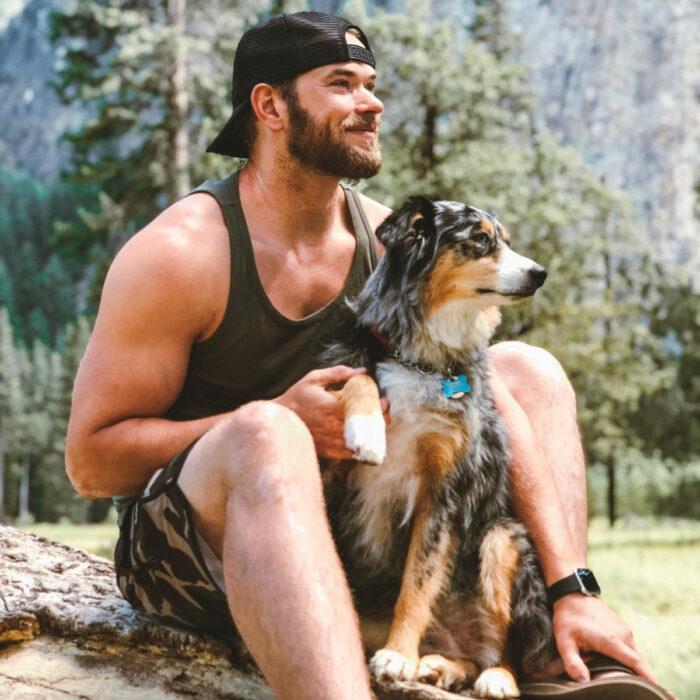Famosos que han adoptado mascotas, perros o gatos; Kellan Lutz en la naturaleza con su perro pastor australiano ovejero color café, negro y blanco, Koda