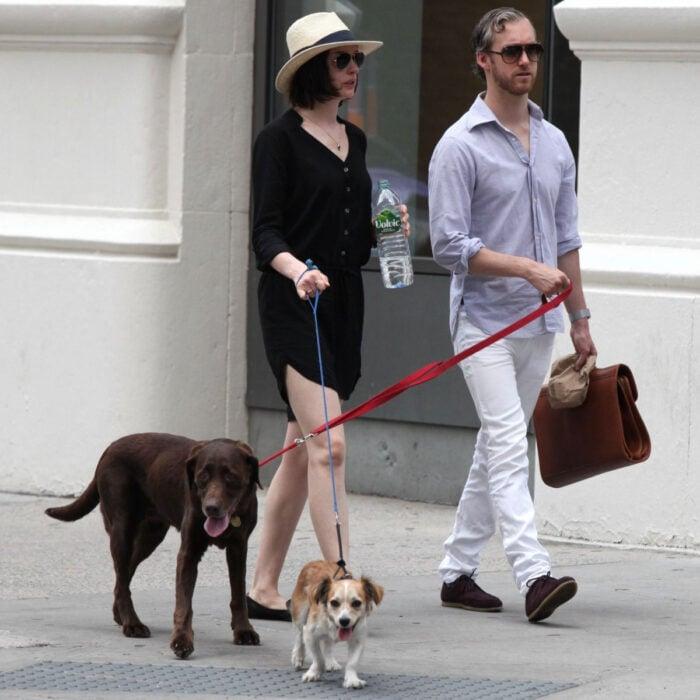 Famosos que han adoptado mascotas, perros o gatos; Anne Hathaway dando un paseo con sus perritos Kenobi y Esmeralda, labrador café y mestizo color miel