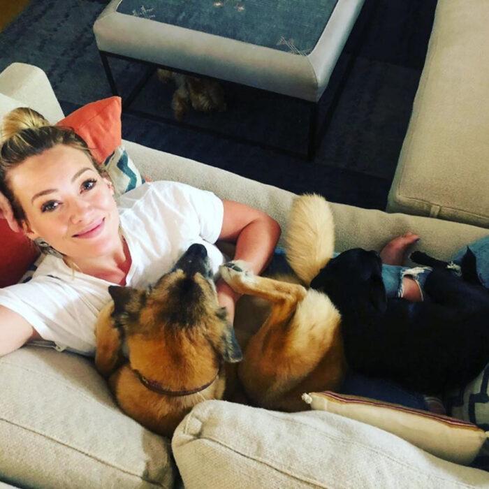 Famosos que han adoptado mascotas, perros o gatos; Hilary Duff sentada en el sillón con sus perritas Lucy y MoMo, color negro y café