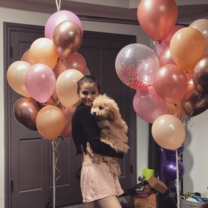 Famosos que han adoptado mascotas, perros o gatos; Selena Gomez en fiesta de cumpleaños con globos y su perrito french poodle café, Winnie